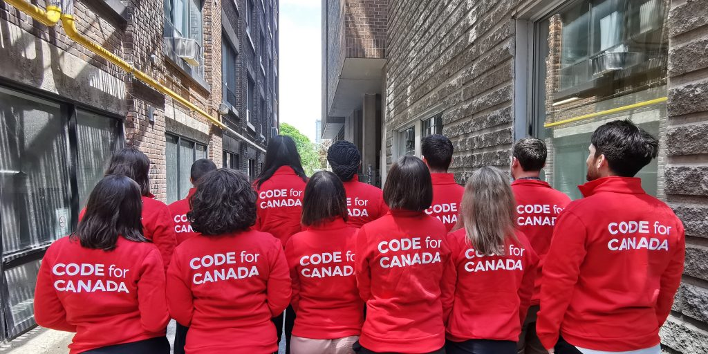 12 people in code for canada jackets with their backs to the camera, looking down an alleyway