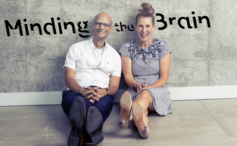 Jim Davies and Kim Hellemans sitting on the floor in front of a cement wall with their podcast logo stencilled on the wall.